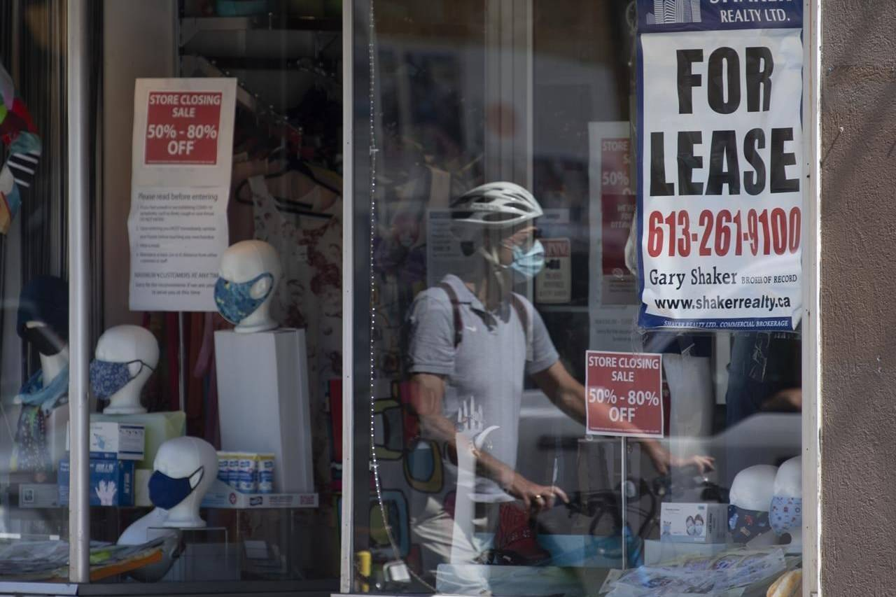 A for lease sign hangs in the window as a cyclist walks past a commercial store, Monday August 31, 2020 in Ottawa. nbsp; THE CANADIAN PRESS/Adrian Wyld