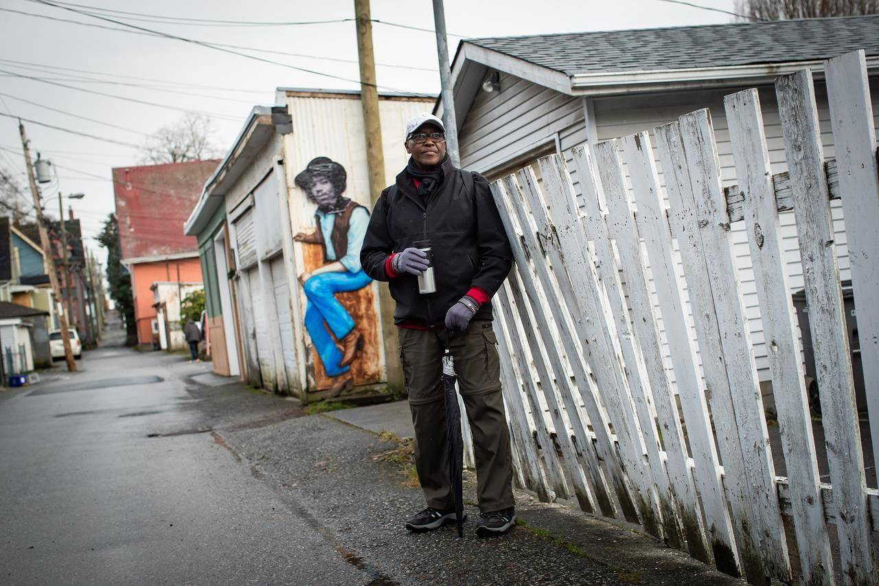 Lama Mugabo, a board member at the Hogan's Alley Society, poses for a photograph at the remaining portion of Hogan's Alley, in Vancouver, on Wednesday, January 27, 2021. The historic black neighbourhood was demolished to make way for the construction of the Georgia and Dunsmuir viaducts in the early 1970s. THE CANADIAN PRESS/Darryl Dyck