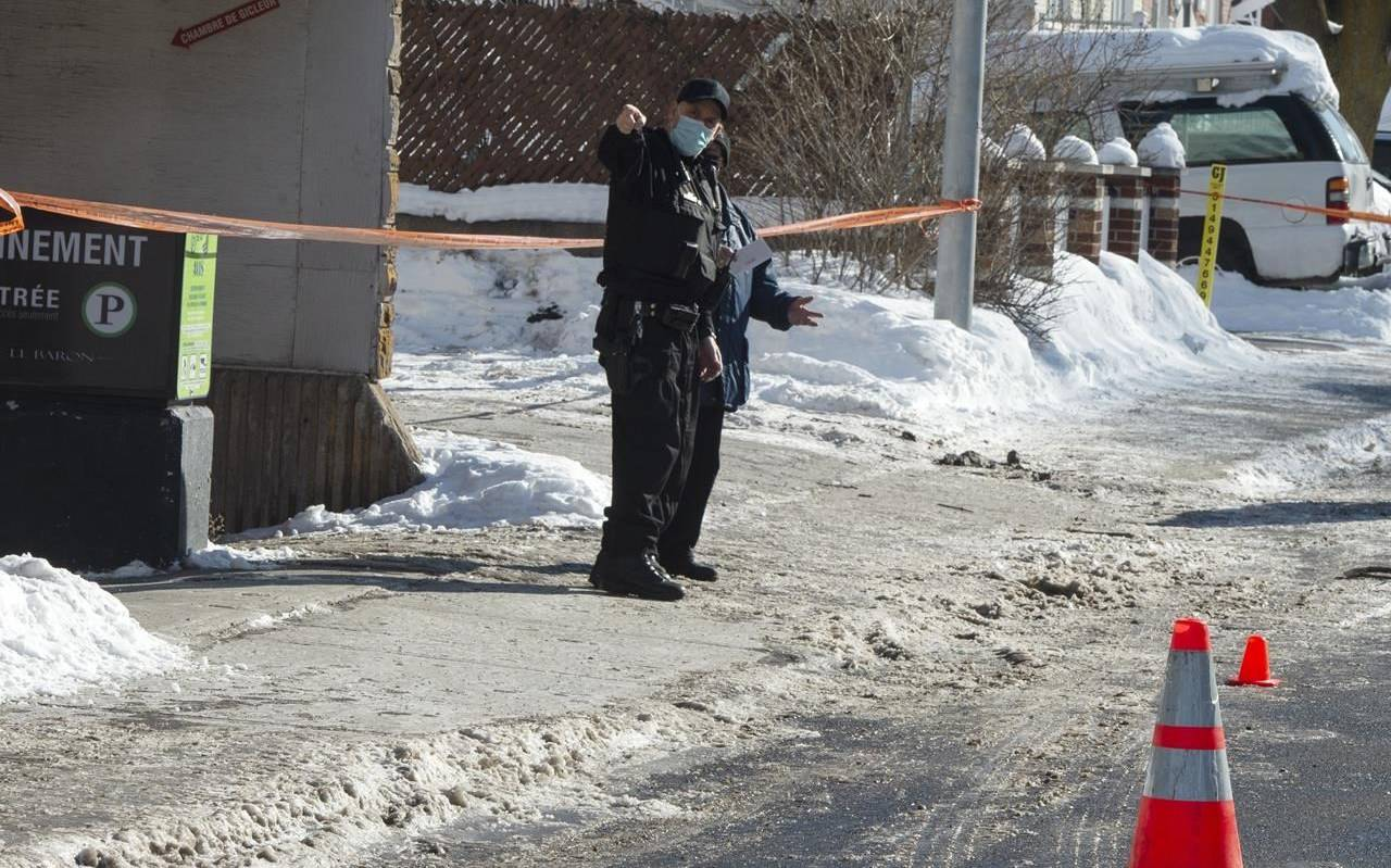 A police officer leaves the crime scene Feb. 8, 2021, in Montreal, where a 15-year-old girl was killed Sunday in a shooting. THE CANADIAN PRESS/Ryan Remiorz