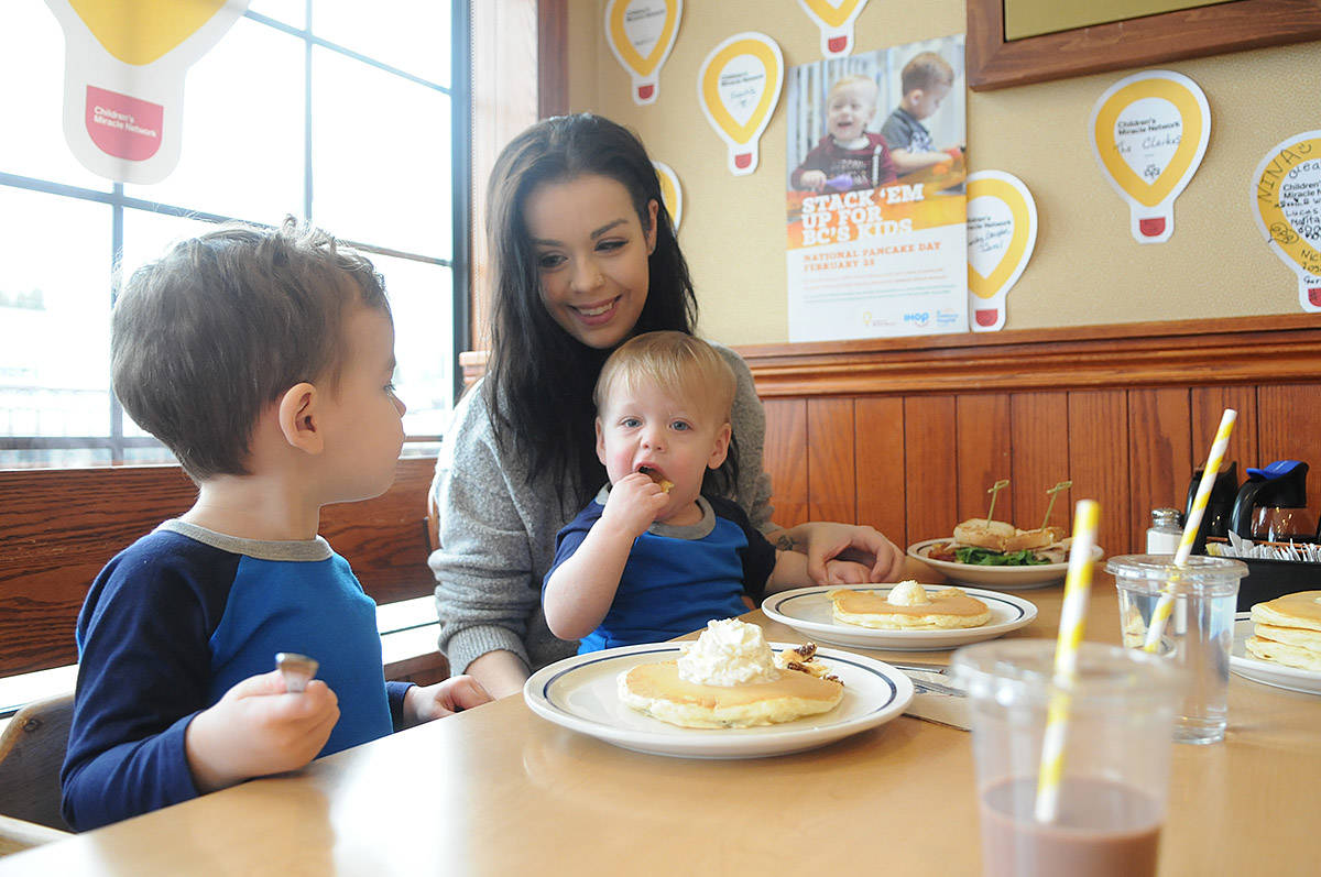 Sauyer Bell sits on mom Shae's lap while having pancakes with her and his two-year-old brother Graeson at IHOP in Chilliwack on Tuesday, Feb. 25, 2020. This photo was taken when Sauyer, who is a BC Children's Hospital patient, was the face on the poster for IHOP's National Pancake Day fundraiser for the hospital last year. (Jenna Hauck/ Chilliwack Progress file)