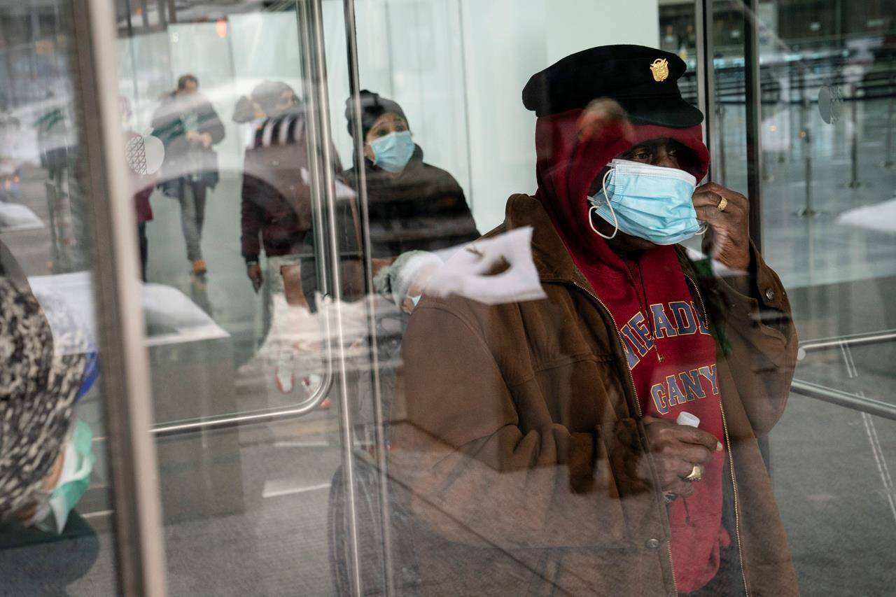 A patient adjusts his face mask as he leaves a COVID-19 vaccination site inside the Jacob K. Javits Convention Center, Wednesday, Feb. 3, 2021, in the Manhattan borough of New York. (AP Photo/John Minchillo)