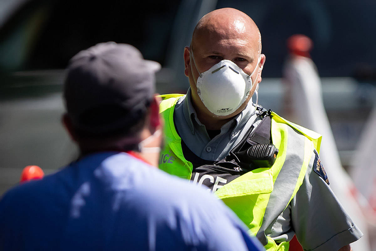 FILE – An RCMP officer wears a face mask while on duty at a COVID-19 testing facility in Burnaby, B.C., on Thursday, August 13, 2020. THE CANADIAN PRESS/Darryl Dyck