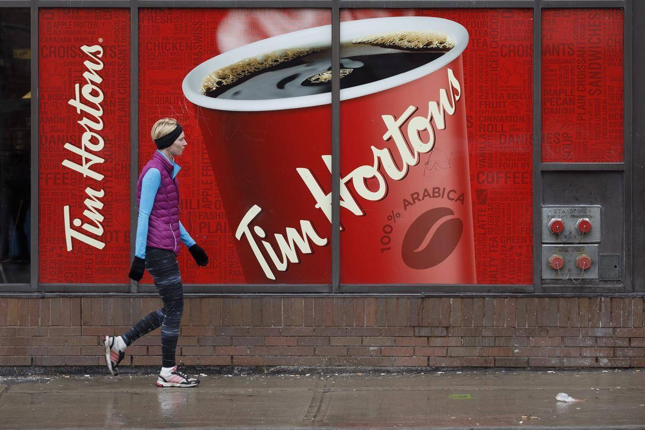 A woman passes by a Tim Hortons restaurant in Toronto on March 6, 2020. Restaurant Brands International Inc. reported its fourth-quarter profit and revenue fell compared with a year ago. THE CANADIAN PRESS/Cole Burston