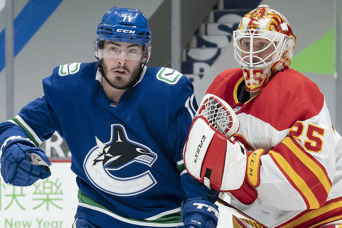 Calgary Flames goaltender Jacob Markstrom (25) tires to clear Vancouver Canucks centre Zack MacEwen (71) from in front of the net during second period NHL action in Vancouver, Thursday, Feb. 11, 2021. THE CANADIAN PRESS/Jonathan Hayward