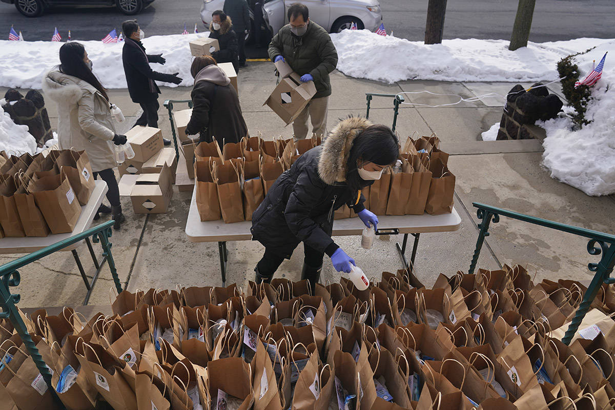 Yoon Kim, center, along with other volunteers from the Korean-American Association of New Jersey, pack bags to give away. Besides masks and hand sanitizer, the bags contain the ingredients for Dduk Guk, a rice cake soup that is traditionally eaten by Koreans to celebrate the new year. (AP Photo/Seth Wenig)