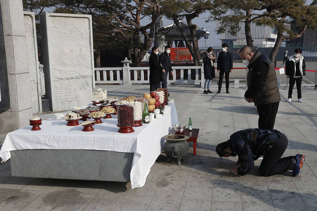 South Korean family members bow to respect for their ancestor in North Korea, on the Lunar New Year at the Imjingak Pavilion in Paju, South Korea, Friday, Feb. 12, 2021. (AP Photo/Lee Jin-man)