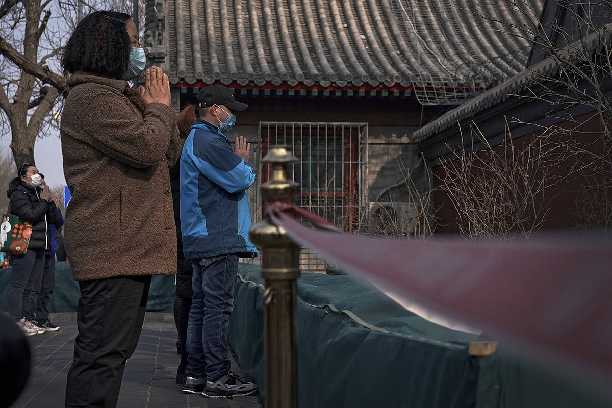 People wearing face masks to help curb the spread of the coronavirus offer prayers outside the closed Yonghegong Lama Temple, usually crowded with worshippers, during the first day of the Lunar New Year in Beijing, Friday, Feb. 12, 2021. (AP Photo/Andy Wong)