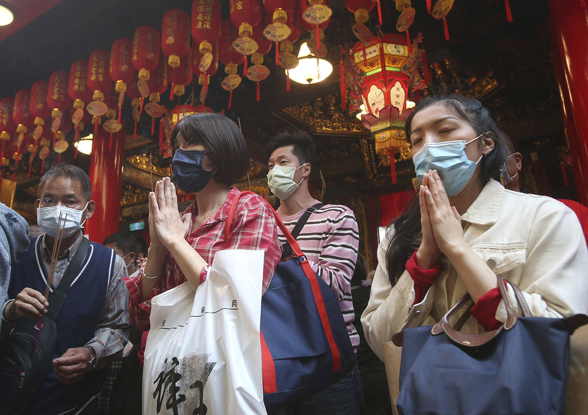 People wear face masks to help curb the spread of the coronavirus as they pray at a temple for the Chinese Lunar New Year, Year of the Ox, in Taipei, Taiwan, Friday, Feb. 12, 2021. (AP Photo/Chiang Ying-ying)