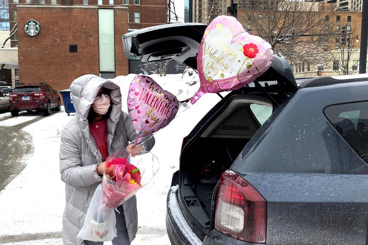 Ellen Yun loads Valentine's Day gifts for her mom, sister and brother in-laws, nephew and her two children Saturday, Feb. 13, 2021, outside a Chicago area grocery store. Yun said she had shopped for her husband earlier. (AP Photo/Charles Rex Arbogast)