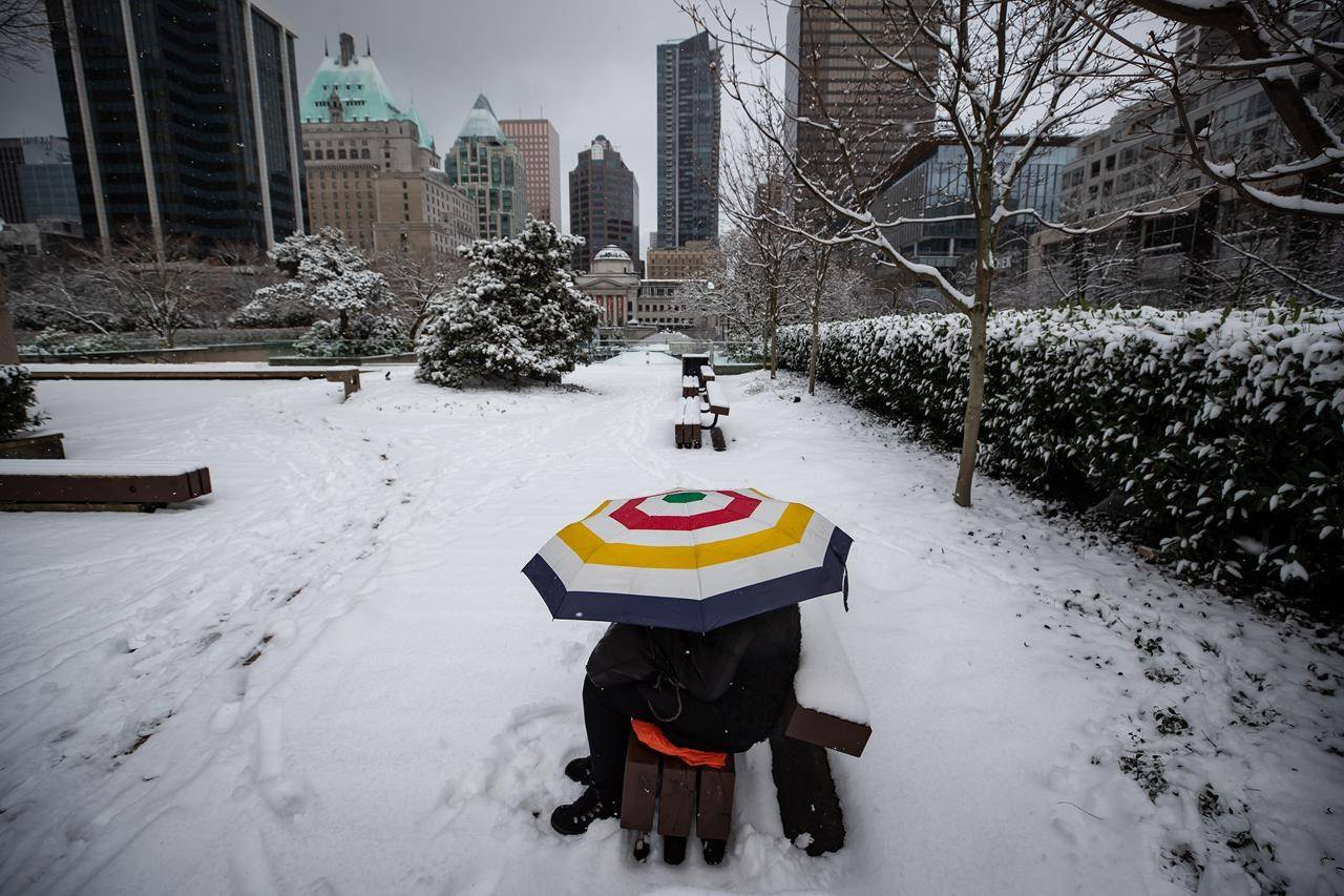 A person sits under an umbrella as snow falls in downtown Vancouver on Saturday, February 13, 2021. A snowfall warning is in effect for much of Metro Vancouver, with five to 10 centimetres expected over the course of the day. THE CANADIAN PRESS/Darryl Dyck