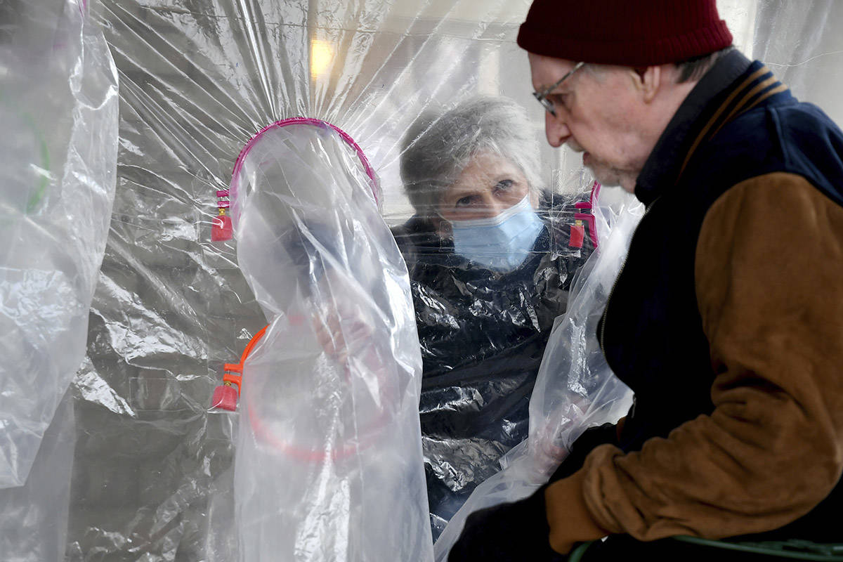 """Lynda Hartman, 75, visits her 77-year-old husband, Len Hartman, in a """"hug tent"""" set up outside the Juniper Village assisted living center in Louisville, Colo., on Wednesday, Feb. 3, 2021. (AP Photo/Thomas Peipert)"""