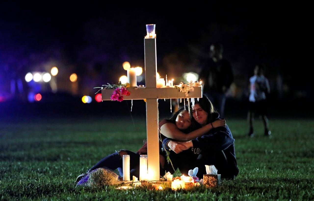 FILE - In this Feb. 15, 2018 file photo, people comfort each other after a candlelight vigil for the victims of the shooting at Marjory Stoneman Douglas High School, in Parkland, Fla. Sorrow is reverberating across the country Sunday, Feb. 14, 2021, as Americans joined a Florida community in remembering the 17 lives lost. (AP Photo/Gerald Herbert, File)