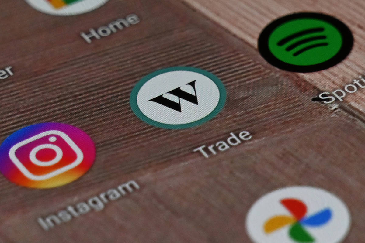 A Wealthsimple Trade app icon is shown on a smartphone on Tuesday, Dec. 15, 2020. Some stock trading platforms say usership has spiked in 2020, as a whipsawing stock market and more time at home has Canadians day trading. THE CANADIAN PRESS/Jesse Johnston