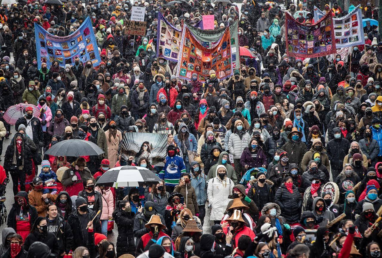 People participate in the annual Women's Memorial March in Vancouver, B.C., Sunday, Feb. 14, 2021. The second wave of the COVID-19 pandemic did not stop a rising tide of reports of domestic violence, experts say, warning that the stress of life in lockdown continues to put victims at risk. THE CANADIAN PRESS/Darryl Dyck