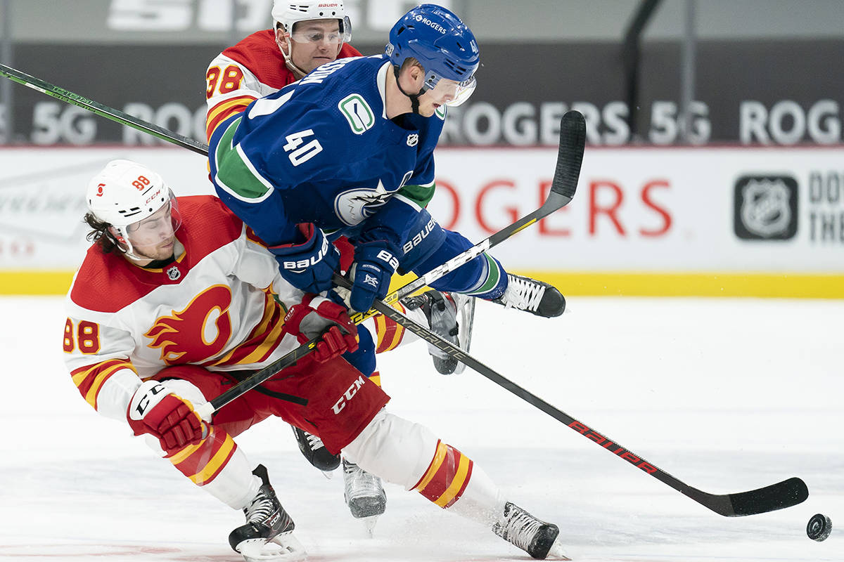 Vancouver Canucks centre Elias Pettersson (40) fights for control of the puck with Calgary Flames left wing Andrew Mangiapane (88) and Byron Froese (38) during first period NHL action in Vancouver, Monday, Feb. 15, 2021. THE CANADIAN PRESS/Jonathan Hayward