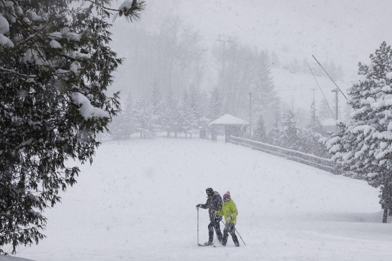 People snowshoe at the foot of the shutdown slopes of Blue Mountain Ski Resort in The Blue Mountains, Ont., Saturday, Dec. 26, 2020. THE CANADIAN PRESS/Cole Burston