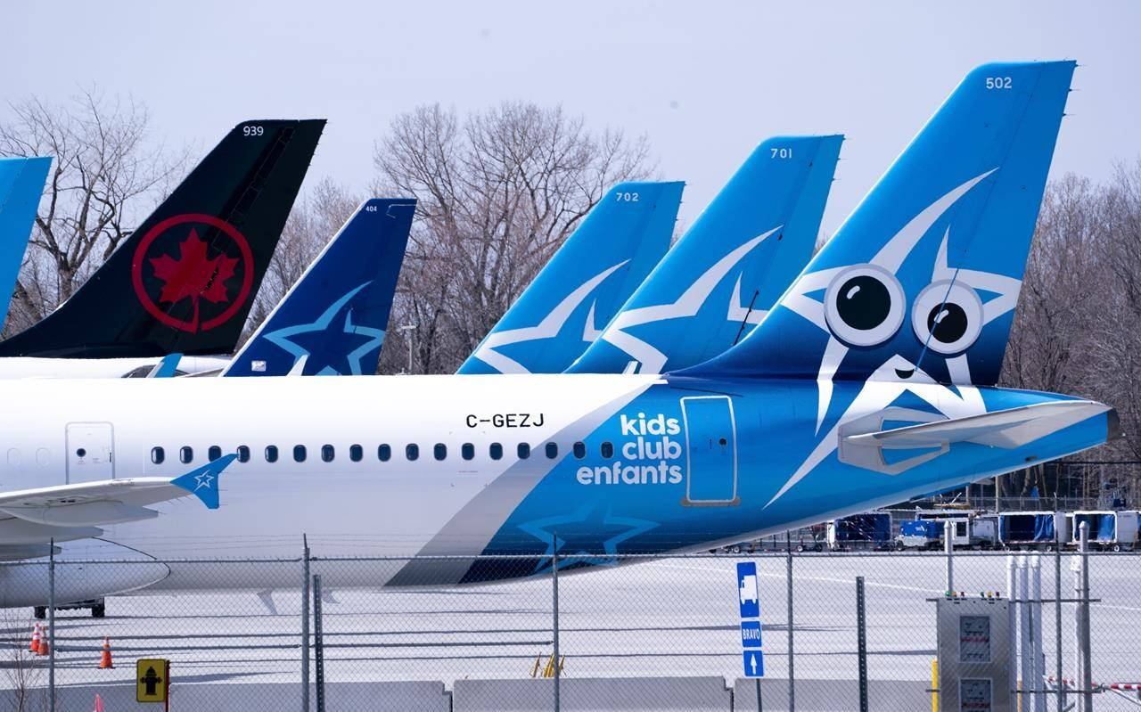 Air Transat and Air Canada aircraft are seen on the tarmac at Montreal-Trudeau International Airport in Montreal, on Wednesday, April 8, 2020. THE CANADIAN PRESS/Paul Chiasson