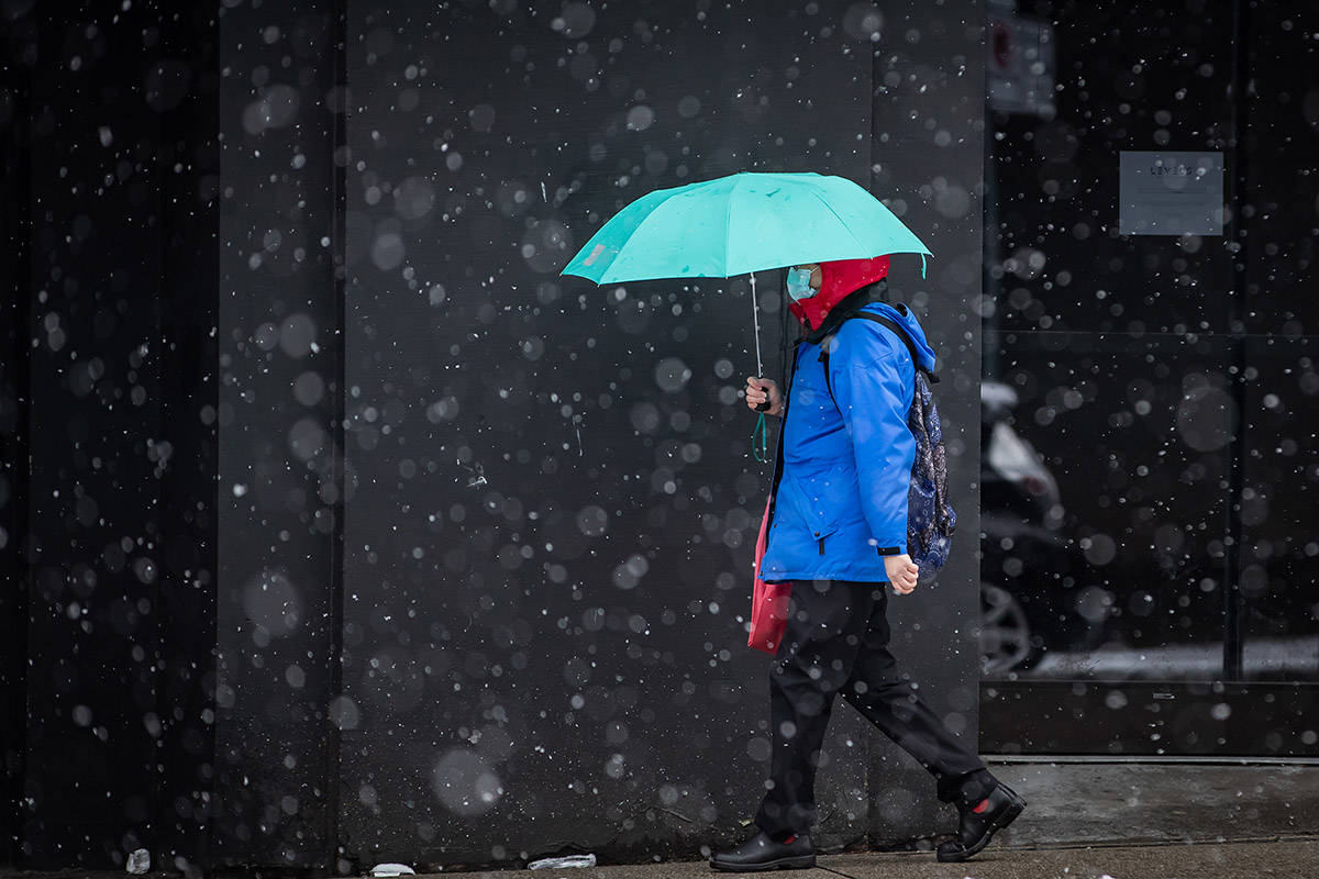 A pedestrian wearing a mask to curb the spread of COVID-19 uses an umbrella as snow falls in downtown Vancouver on Saturday, February 13, 2021. THE CANADIAN PRESS/Darryl Dyck