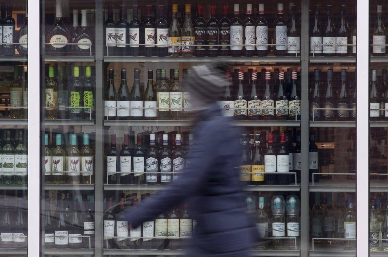 A person walks past shelves of bottles of alcohol on display at an LCBO in Ottawa on March 19, 2020. THE CANADIAN PRESS/Adrian Wyld