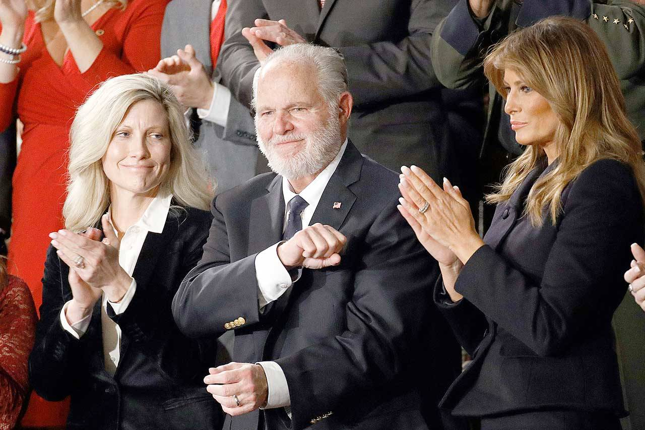 FILE - In this Feb. 4, 2020 file photo, Rush Limbaugh reacts as first Lady Melania Trump, and his wife Kathryn, applaud, as President Donald Trump delivers his State of the Union address to a joint session of Congress on Capitol Hill in Washington. Limbaugh, the talk radio host who became the voice of American conservatism, has died. (AP Photo/Patrick Semansky)
