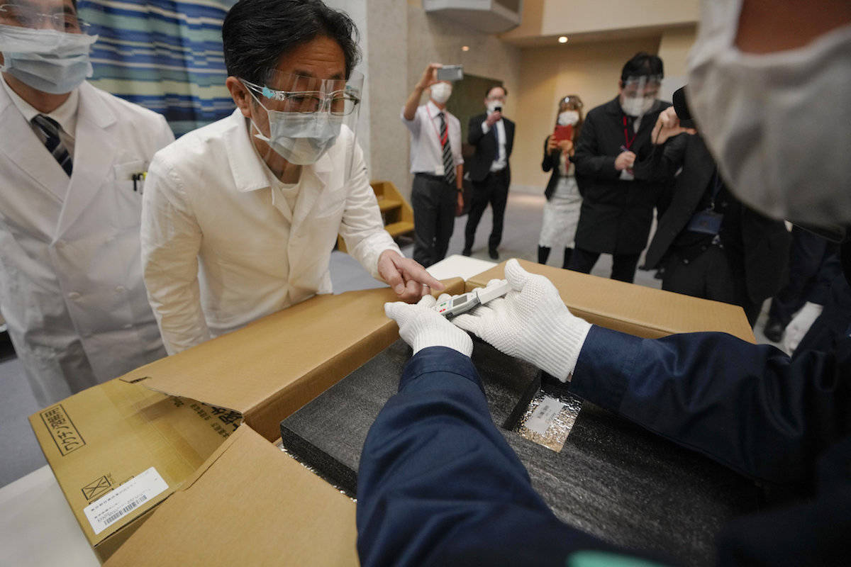 COVID-19 vaccine is checked on delivery to a Tokyo hospital Tuesday, Feb. 16, 2021. Japan's COVID-19 vaccinations are scheduled to begin Wednesday after the government granted belated first approval to a shot co-developed by Pfizer Inc. (Kimimasa Mayama/Pool Photo via AP)