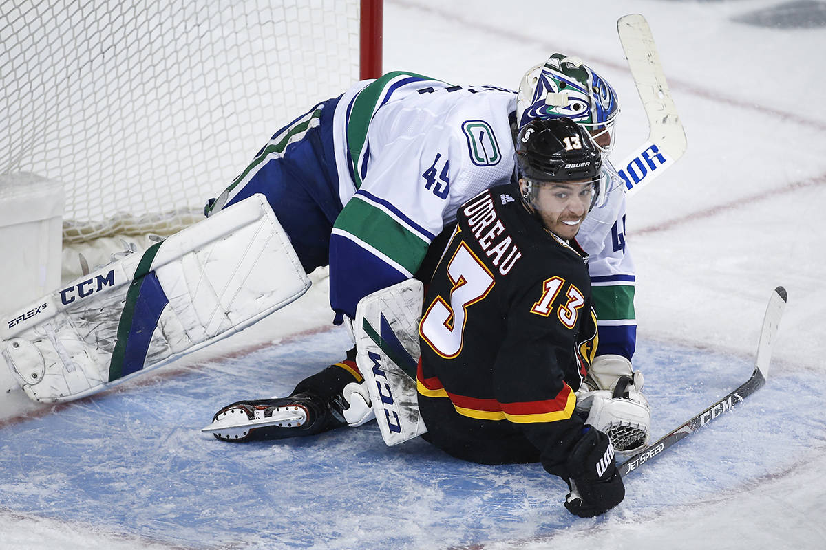 Vancouver Canucks goalie Braden Holtby is knocked off his skates by Calgary Flames' Johnny Gaudreau during third period NHL hockey action in Calgary, Wednesday, Feb. 17, 2021.THE CANADIAN PRESS/Jeff McIntosh