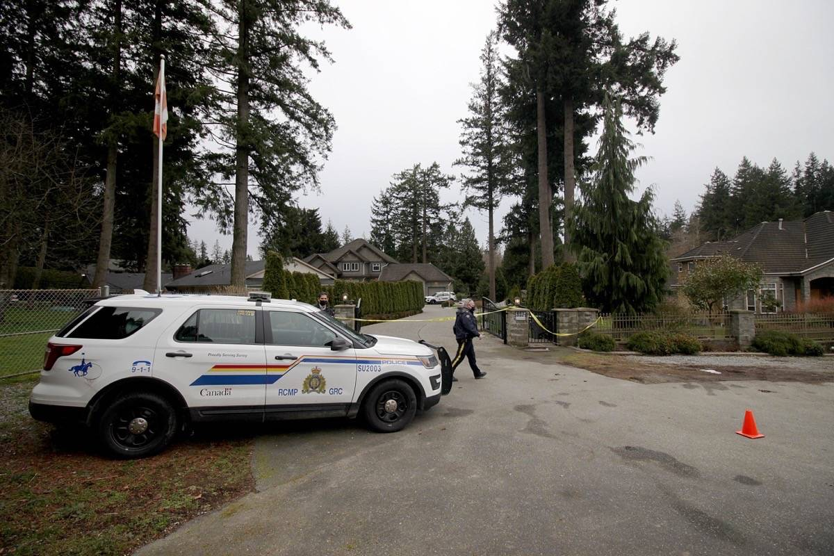 """Surrey RCMP had a home in the 5500-block of 125th Street behind tape Thursday morning after they were called for an assault Wednesday (Feb. 17) around 8 p.m. Police said officers found a """"critically injured"""" man outside the home when they arrived, but he later died at the scene. (Photo: Lauren Collins)"""