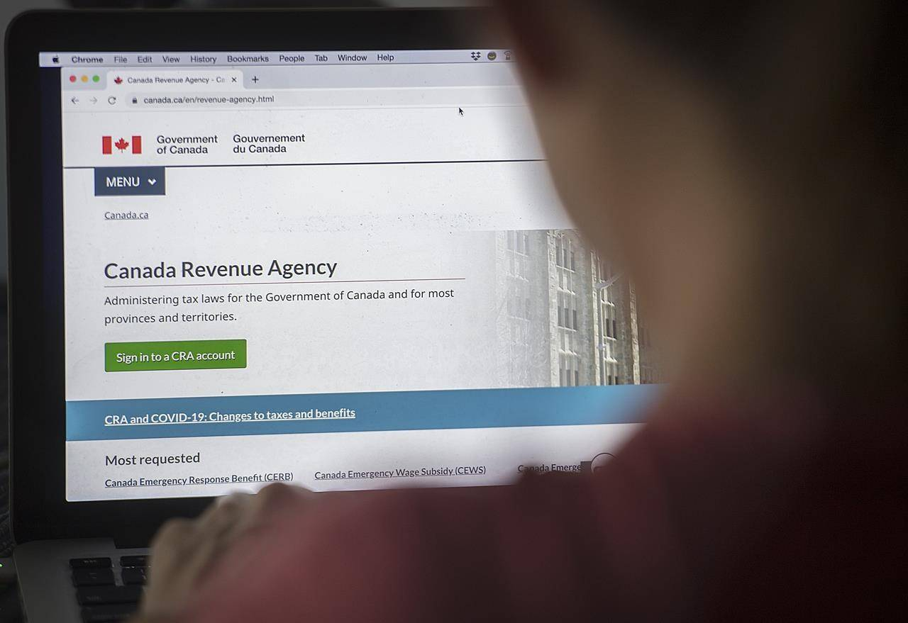 A person looks at a Canada Revenue Agency homepage in Montreal, Sunday, August 16, 2020. The Canada Revenue Agency says some taxpayers were locked out of their online accounts even though it wasn't the victim of a cyberattack. THE CANADIAN PRESS/Graham Hughes