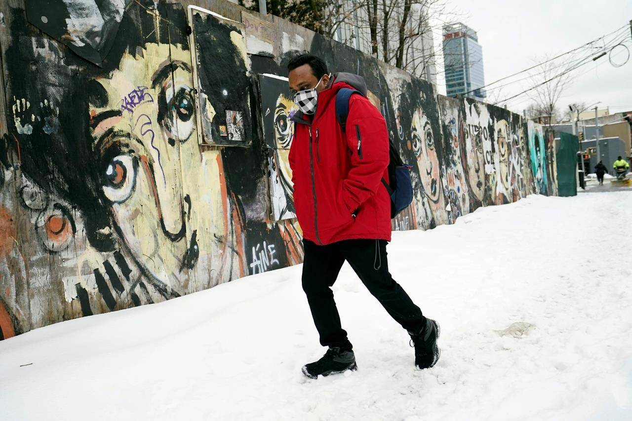 A man makes his way down a snowy street before it was cleared after after several inches of snow, sleet and freezing rain fell, Thursday, Feb. 18, 2021, in New York. (AP Photo/Kathy Willens)