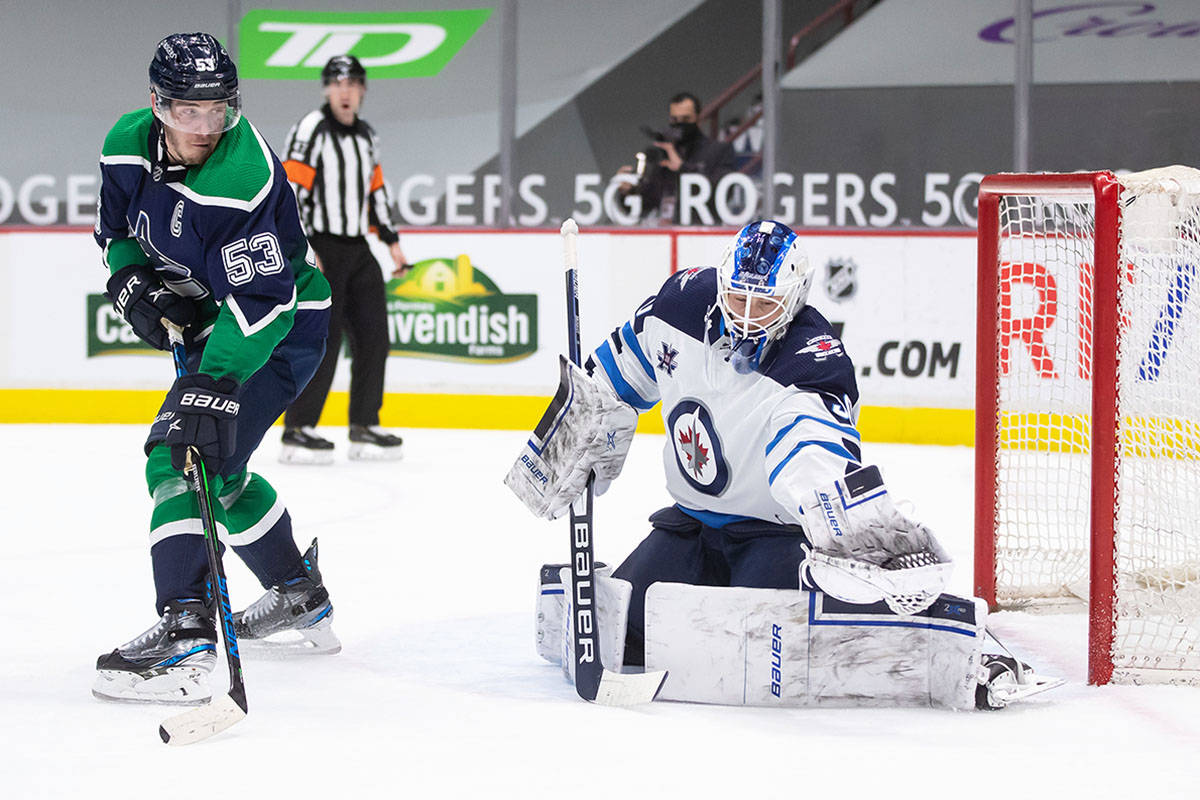 Winnipeg Jets goalie Laurent Brossoit, right, makes a glove save as Vancouver Canucks' Bo Horvat watches during the second period of an NHL hockey game in Vancouver, on Friday, Feb. 19, 2021. THE CANADIAN PRESS/Darryl Dyck