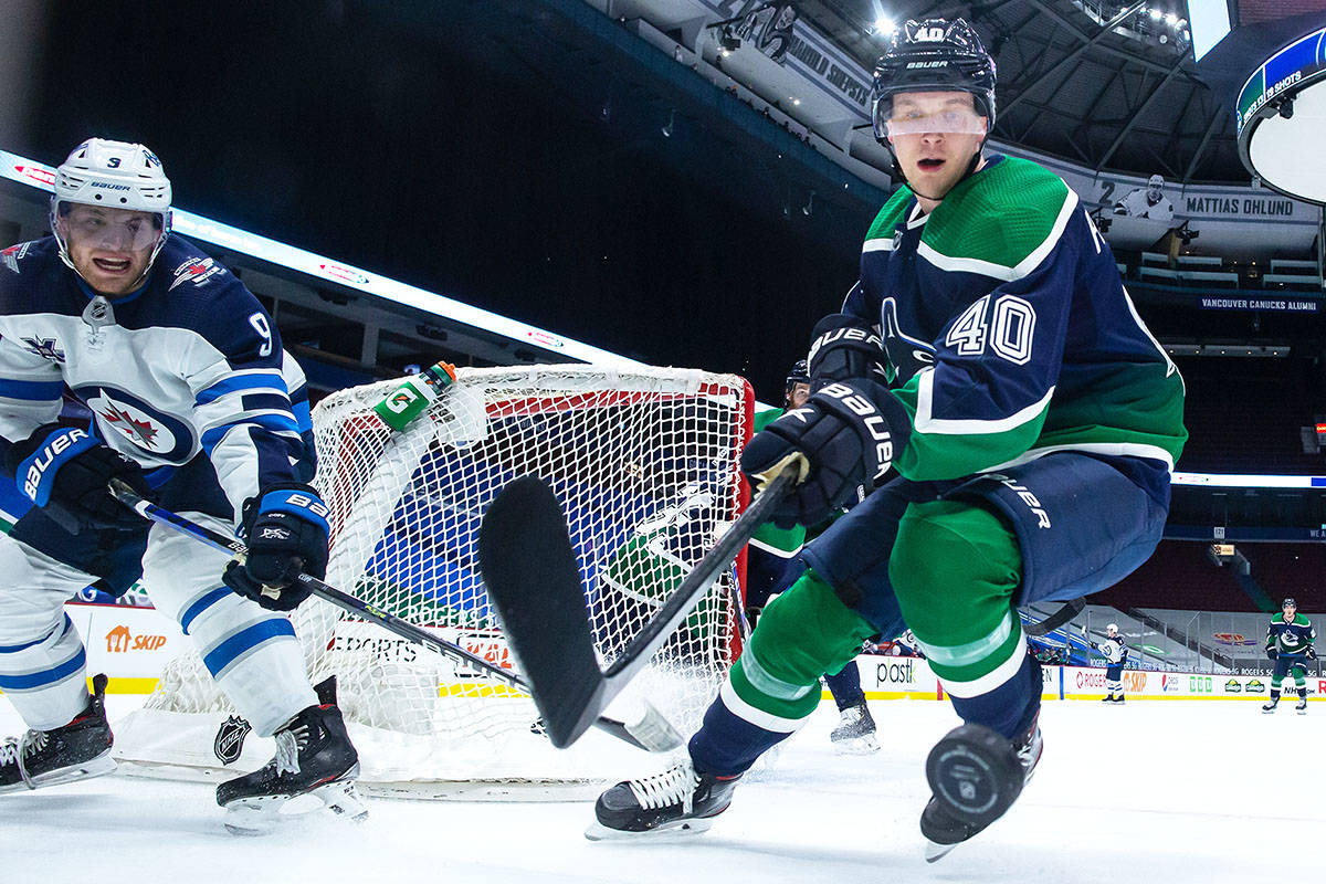 Vancouver Canucks' Elias Pettersson (40), of Sweden, reaches for the puck in front of Winnipeg Jets' Andrew Copp (9) during the second period of an NHL hockey game in Vancouver, on Friday, Feb. 19, 2021. THE CANADIAN PRESS/Darryl Dyck