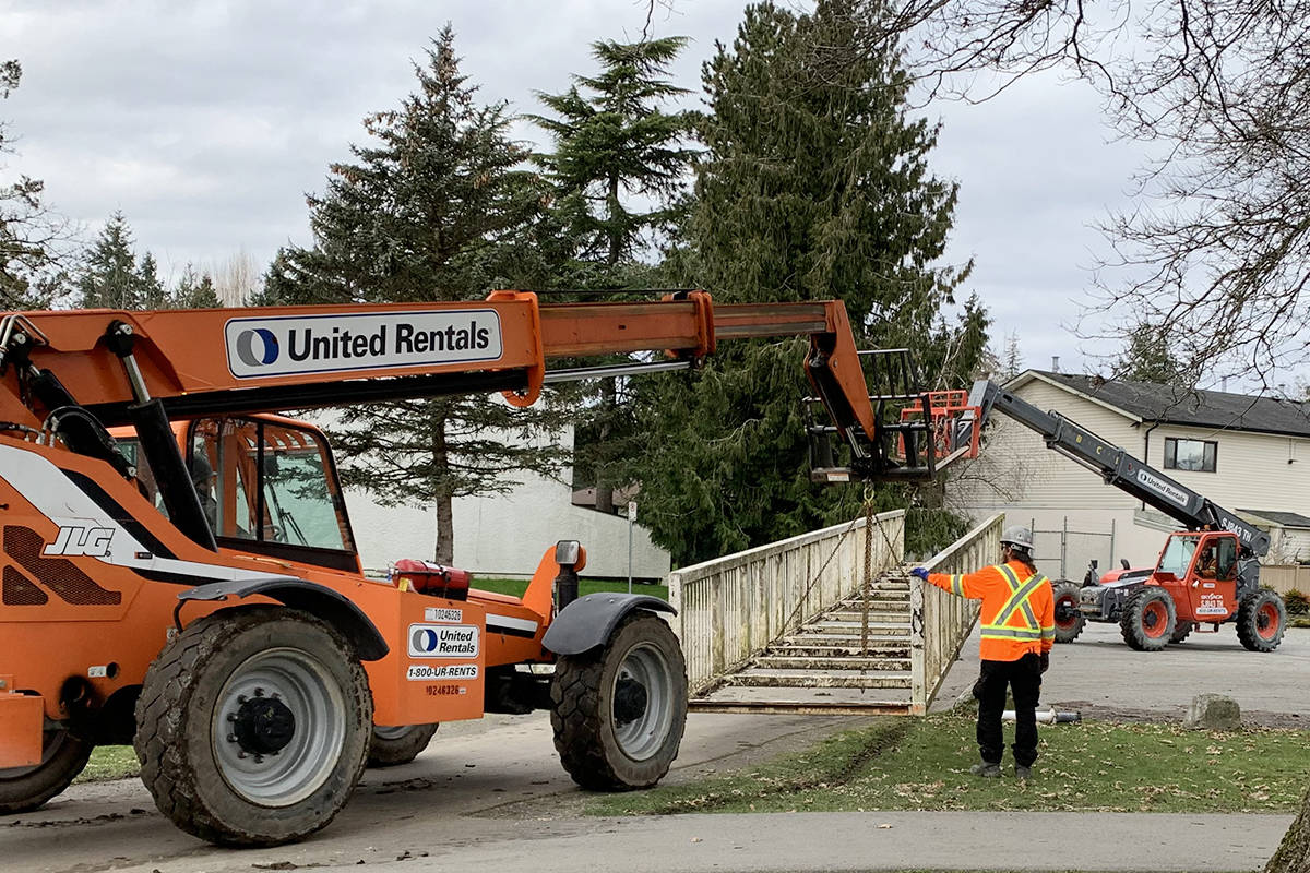 To prevent possible contamination of the Nicomekl River, Langley City crews lifted out this pedestrian bridge for sandblasting and refinishing (Photo by Steve Brown/Langley City)