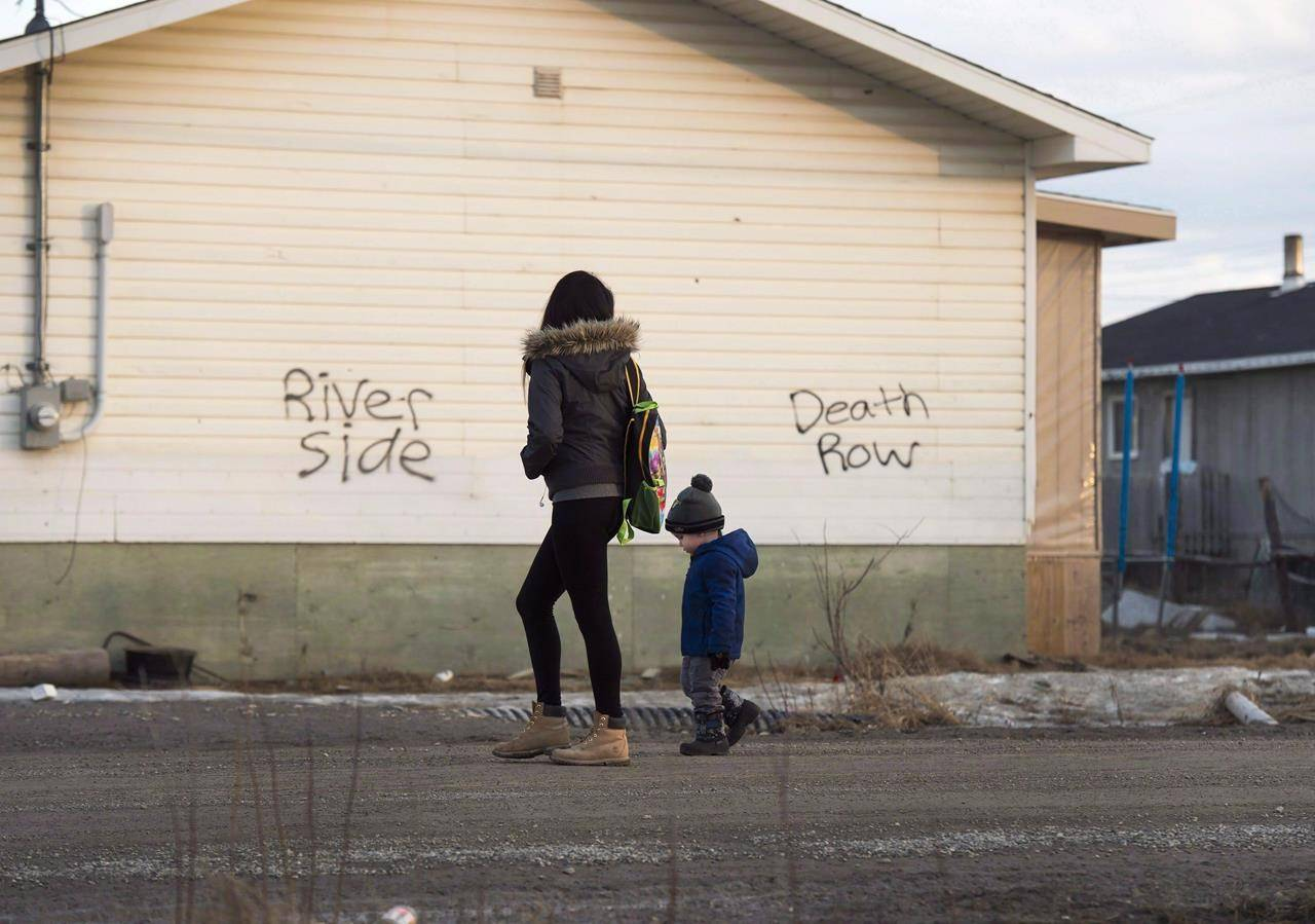 A woman and child walk down a street in the northern Ontario First Nations reserve in Attawapiskat, Ont., on Monday, April 16, 2016. THE CANADIAN PRESS/Nathan Denette