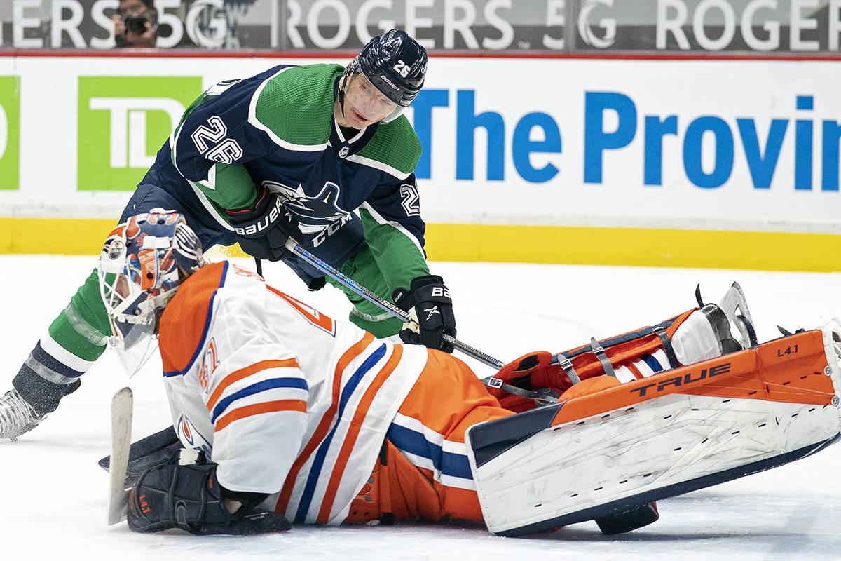 Vancouver Canucks left wing Antoine Roussel (26) tries to get a shot past Edmonton Oilers goaltender Mike Smith (41) during second period NHL action in Vancouver, Tuesday, Feb. 23, 2021. THE CANADIAN PRESS/Jonathan Hayward