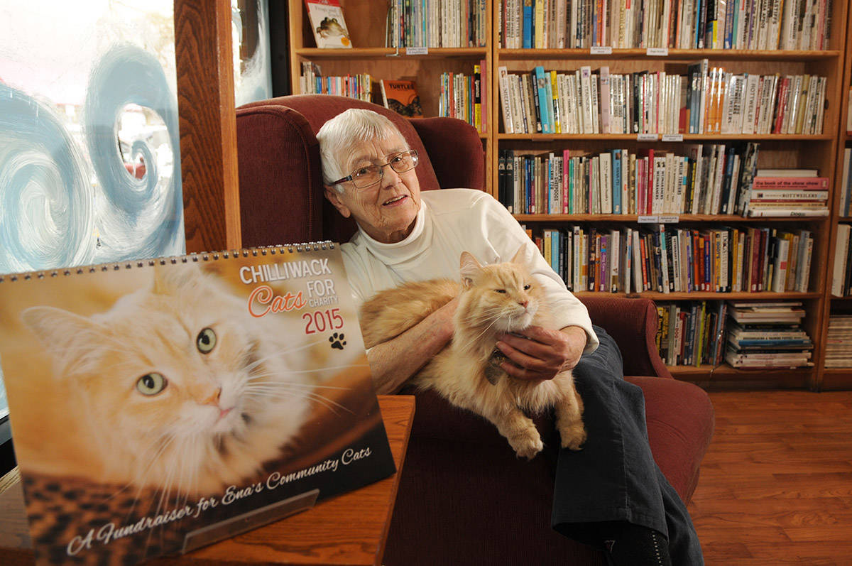 Nietzsche, the ginger cat who worked at The Book Man, poses for a photo with Ena Vermerris on Dec. 4, 2014. Nietzsche died on Monday, Feb. 22, 2021. (Jenna Hauck/ Chilliwack Progress file)