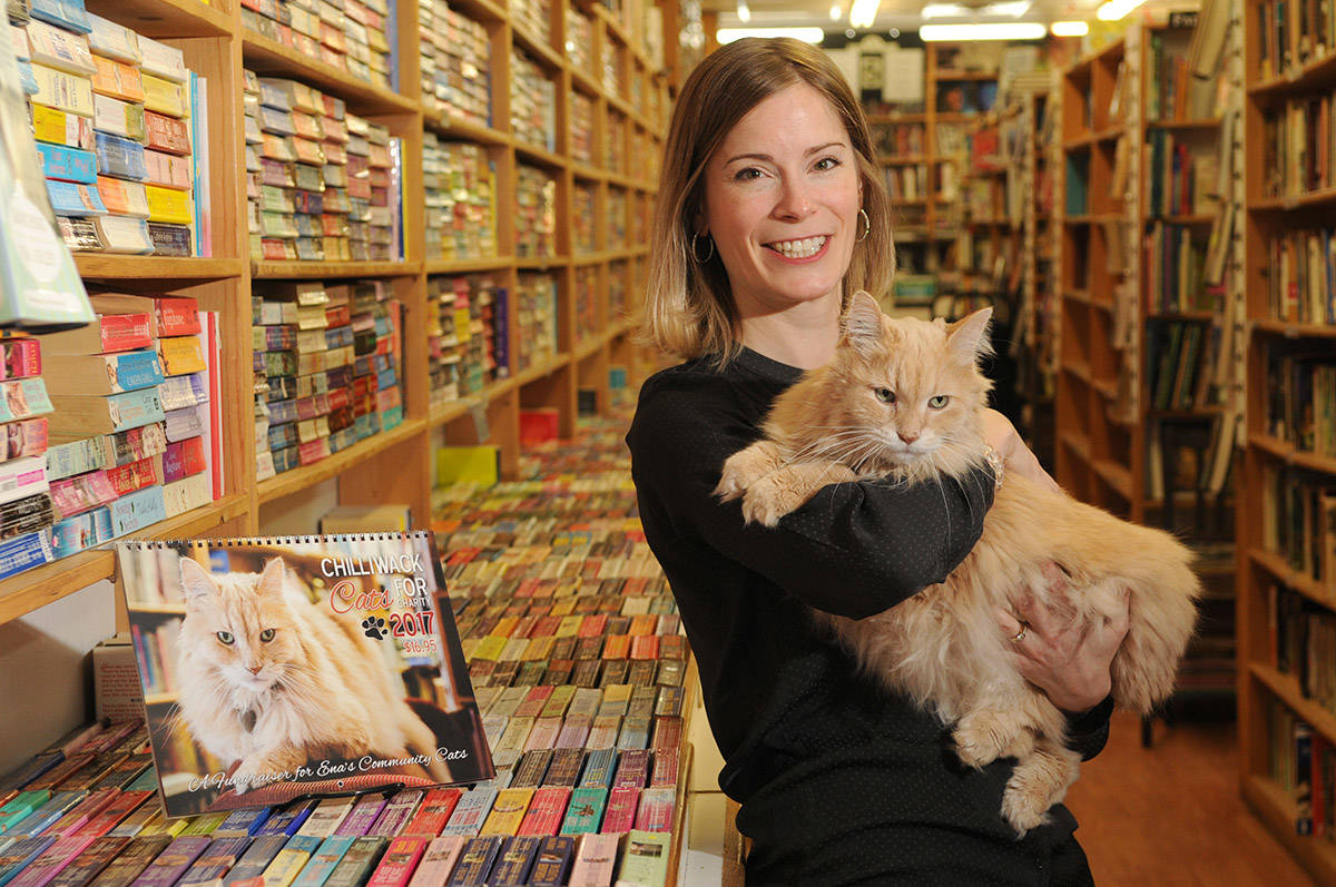 Nietzsche, the ginger cat who worked at The Book Man, poses for a photo with Amber Price on Dec. 15, 2016. Nietzsche died on Monday, Feb. 22, 2021. (Jenna Hauck/ Chilliwack Progress file)