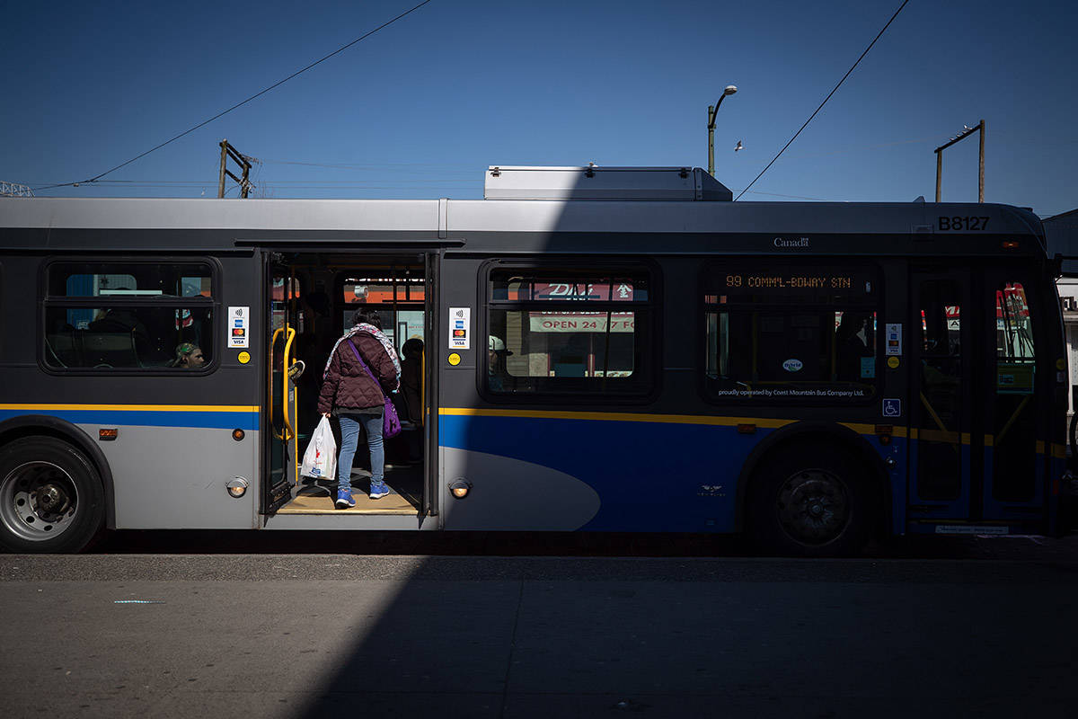 A woman boards a transit bus through rear doors, in Vancouver, on Friday, March 20, 2020. THE CANADIAN PRESS/Darryl Dyck