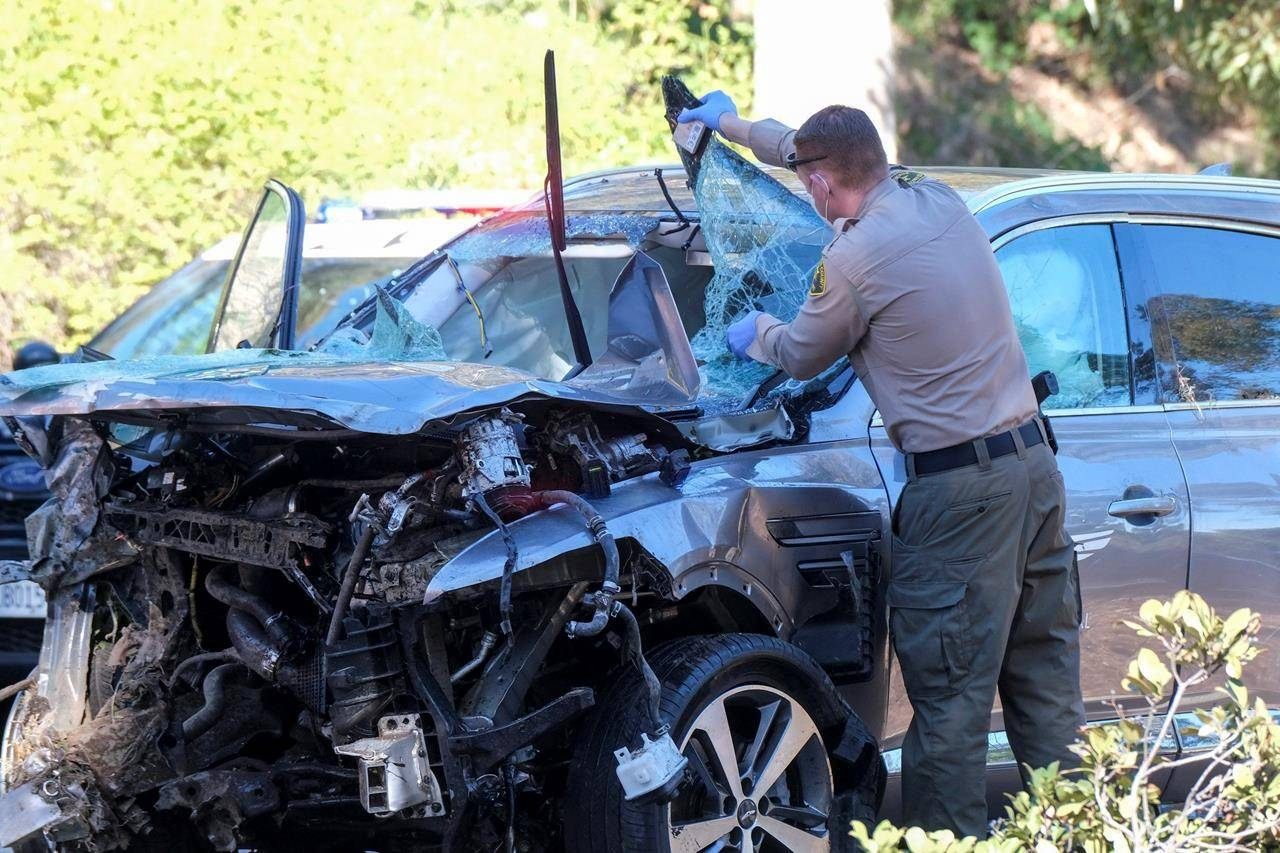 A law enforcement officer looks over a damaged vehicle following a rollover accident involving golfer Tiger Woods, Tuesday, Feb. 23, 2021, in the Rancho Palos Verdes suburb of Los Angeles. (AP Photo/Ringo H.W. Chiu)