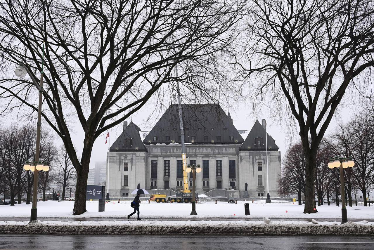 A pedestrian walks past the Supreme Court of Canada in Ottawa on Thursday, Nov. 26, 2020. Canada's top court has decided against hearing appeals brought to it by Bell Canada and a number of cable companies. THE CANADIAN PRESS/Sean Kilpatrick