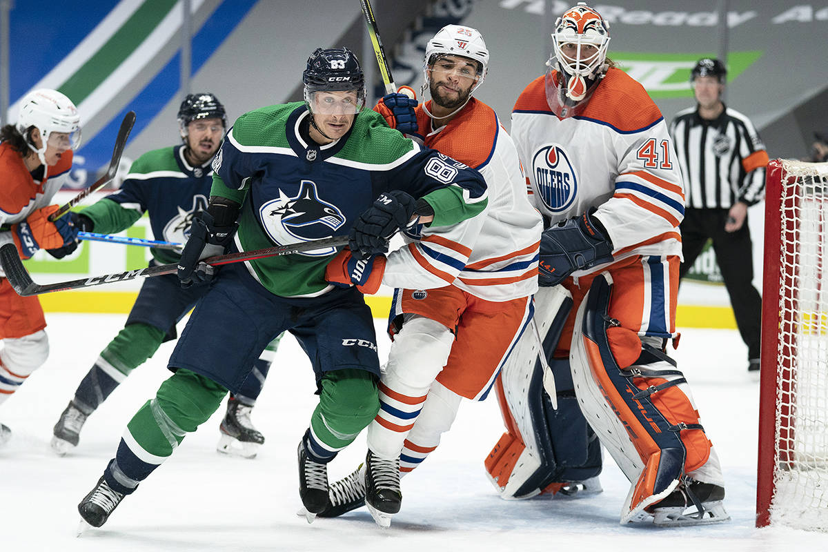 Edmonton Oilers defenceman Darnell Nurse (25) tries to clear Vancouver Canucks centre Jay Beagle (83) from in front of Oilers goaltender Mike Smith (41) during second period NHL action in Vancouver, Thursday, Feb. 25, 2021. THE CANADIAN PRESS/Jonathan Hayward