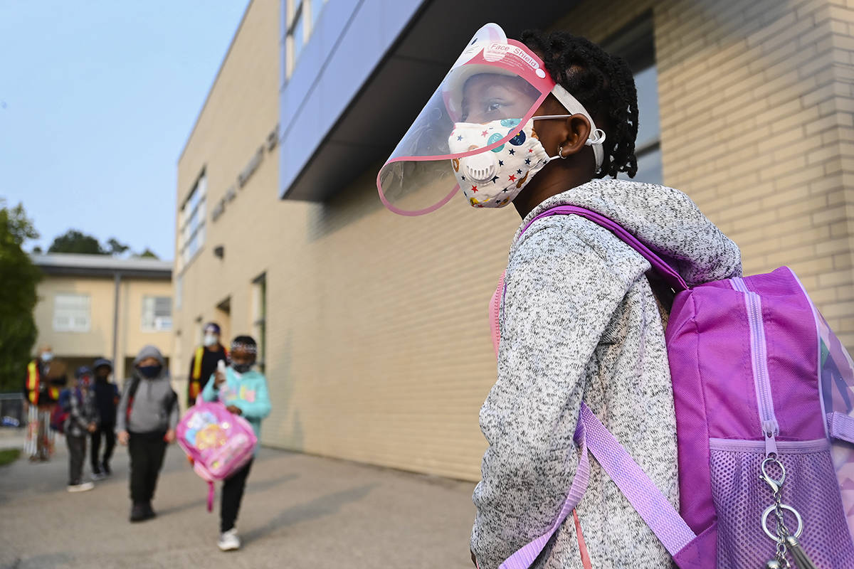 Five-year-old Nancy Murphy wears a full mask and face shield as she waits in line for her kindergarten class to enter school during the COVID-19 pandemic on Tuesday, September 15, 2020. THE CANADIAN PRESS/Nathan Denette