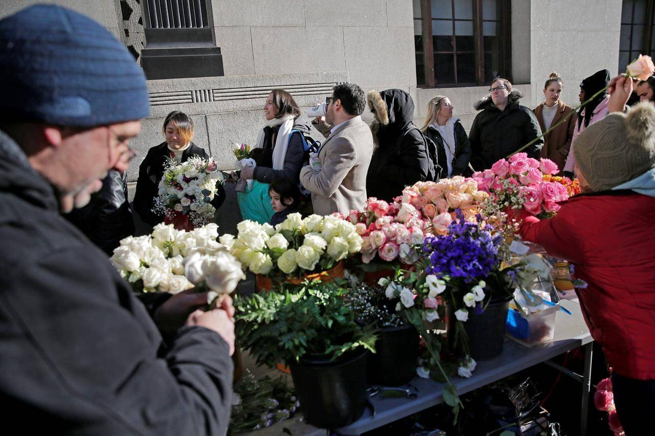 Florists prepare bouquets as people wait in a long line to enter the New York City Marriage Bureau, on Valentine's Day. (AP Photo/Seth Wenig)