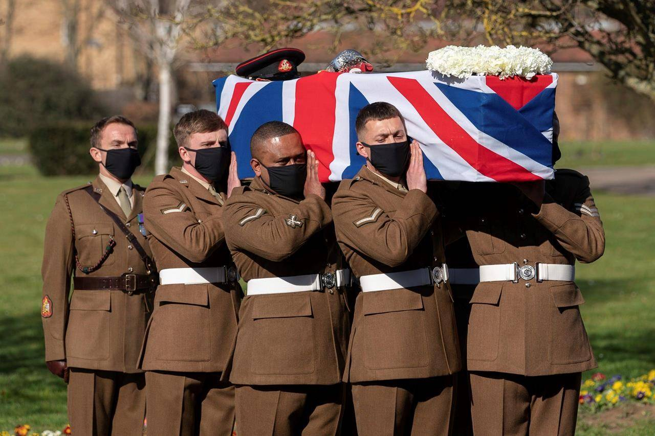 The coffin of Captain Sir Tom Moore is carried by members of the Armed Forces during his funeral, at Bedford Crematorium, in Bedford, England, Saturday, Feb. 27, 2021. (Joe Giddens/Pool Photo via AP)