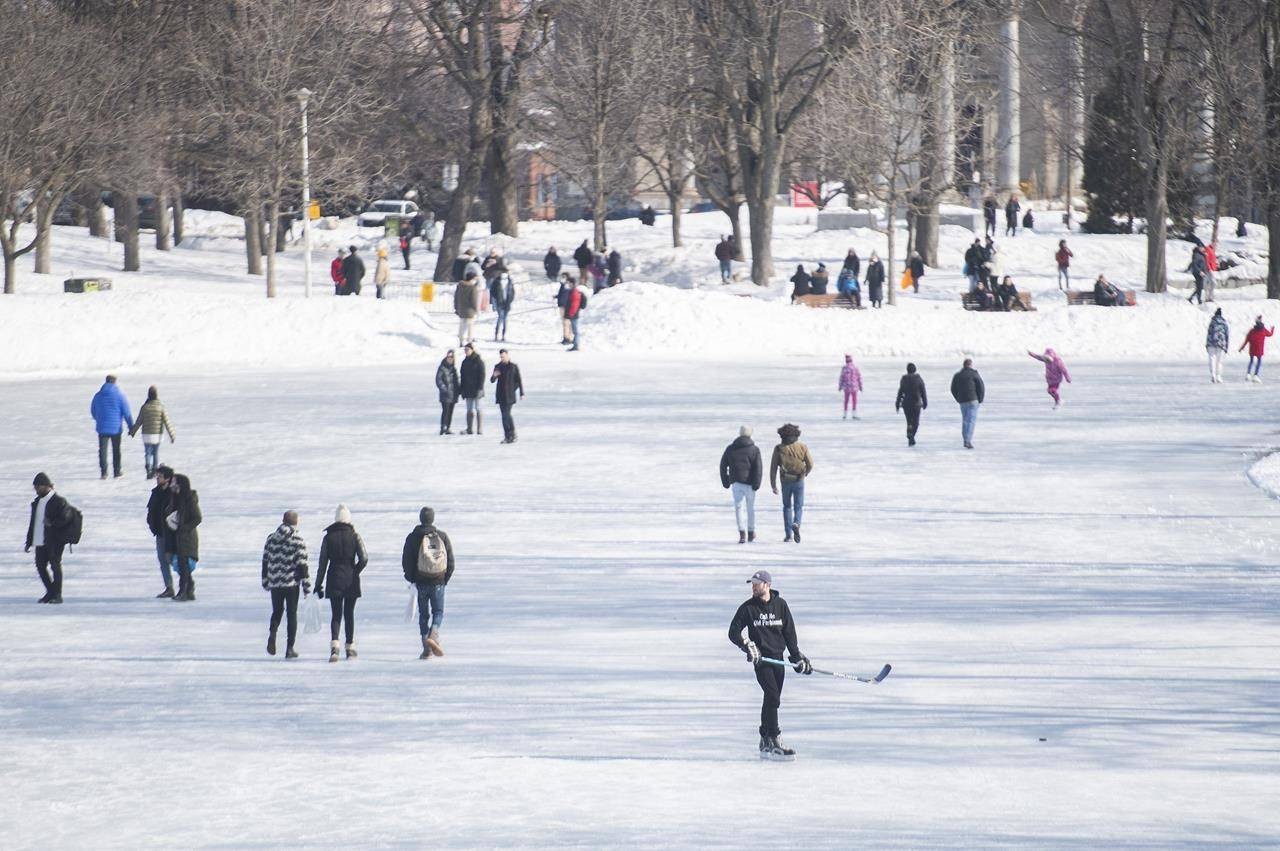 People walk and skate on a thawing lake in a park on a mild winter day in Montreal, Sunday, February 28, 2021, as the COVID-19 pandemic continues in Canada and around the world. THE CANADIAN PRESS/Graham Hughes