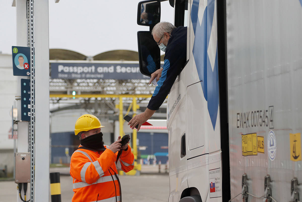FILE  - In this Friday, Jan 1, 2021 file photo, a lorry driver's documents are scanned on a phone as he passes a checkpoint for the train through the Eurotunnel link with Europe in Folkestone, England. One month after Britain made a New Year split from the European Union's economic embrace, businesses that once traded freely are getting used to frustrating checks, delays and red tape. Meat exporters say shipments have rotted in trucks awaiting European health checks. Scottish fishermen have protested at Parliament over the catch they can no longer sell to the continent because of byzantine new paperwork. (AP Photo/Frank Augstein, File)