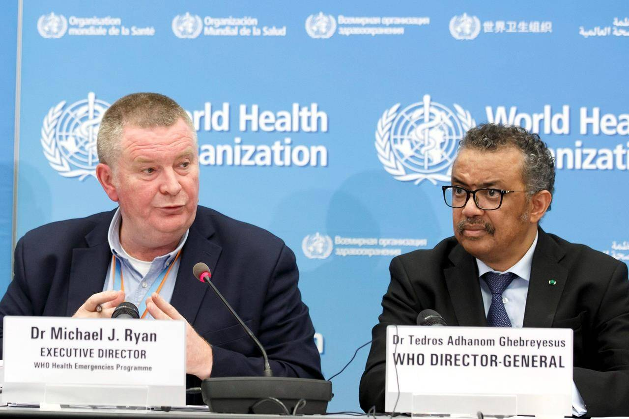 "FILE - In this Monday, Feb. 24, 2020 file photo, Michael Ryan, left, Executive Director of WHO's Health Emergencies programme, next to Tedros Adhanom Ghebreyesus, right, Director General of the World Health Organization (WHO), addresses a press conference about the update on COVID-19 at the World Health Organization headquarters in Geneva, Switzerland. The emergencies chief of the World Health Organization said on Monday March 1, 2021, it was ""premature"" and ""unrealistic"" to think the pandemic might be stopped by the end of the year, but that the recent arrival of effective vaccines could at least help dramatically reduce hospitalizations and death. (Salvatore Di Nolfi/Keystone via AP, File)"