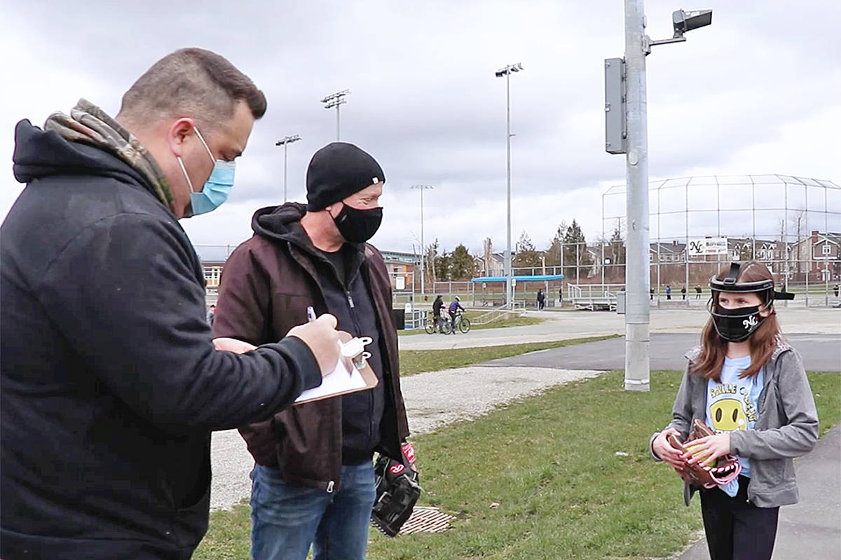 A player is checked in prior to the start of play in a North Langley Softball video produced to demonstrate COVID-19 safety measures are in place (Danica Reed video/special to Langley Advance Times)