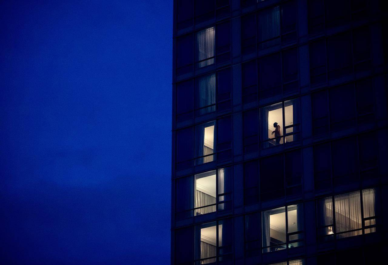 A person is seen in the window of a room at a government-authorized COVID-19 quarantine hotel in Richmond, B.C. on Sunday, February 28, 2021. THE CANADIAN PRESS/Darryl Dyck