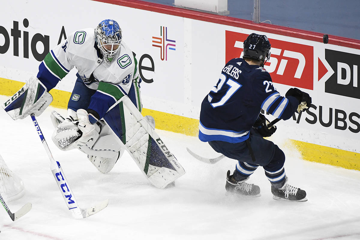 Vancouver Canucks goaltender Thatcher Demko (35) clears the puck past Winnipeg Jets' Nikolaj Ehlers (27) during second period NHL action in Winnipeg on Monday March 1, 2021. THE CANADIAN PRESS/Fred Greenslade