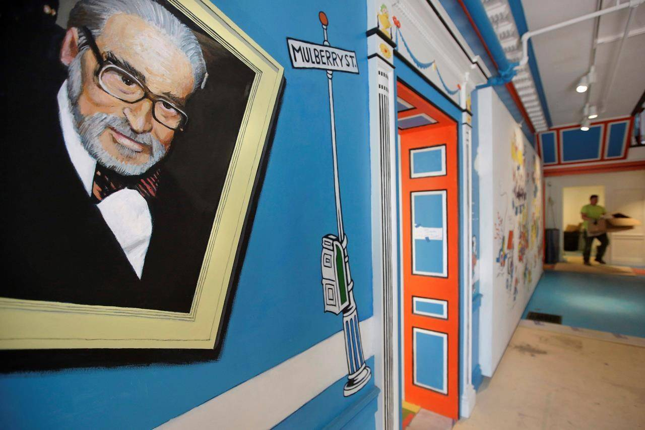 """FILE - In this May 4, 2017, file photo, a mural that features Theodor Seuss Geisel, left, also known by his pen name Dr. Seuss, covers part of a wall near an entrance at The Amazing World of Dr. Seuss Museum, in Springfield, Mass. Dr. Seuss Enterprises, the business that preserves and protects the author and illustrator's legacy, announced on his birthday, Tuesday, March 2, 2021, that it would cease publication of several children's titles including """"And to Think That I Saw It on Mulberry Street"""" and """"If I Ran the Zoo,"""" because of insensitive and racist imagery. (AP Photo/Steven Senne, File)"""